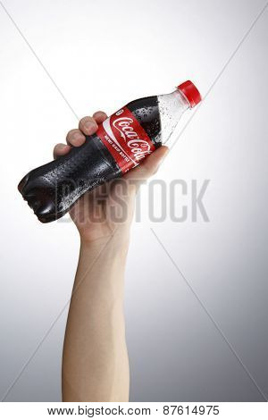 Kuala Lumpur,Malaysia 9th April 2015, Hand hold a bottle Coca-Cola on white background. Coca Cola drinks are produced and manufactured by The Coca-Cola Company.
