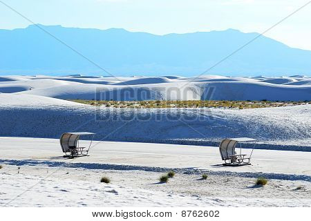 Two picnic tables at White Sands National Monument in New Mexico with the Organ Mountain range in the background. poster