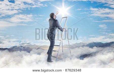 Businessman climbing on ladder in the clouds poster