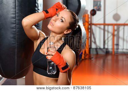 Female kickboxer drinks water