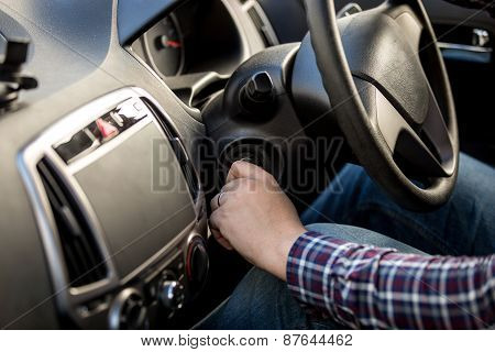 Driver Turning Ignition Key In Right-hand Drive Car