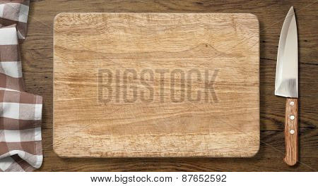 Cutting board and knife on old wood table with picnic tablecloth background