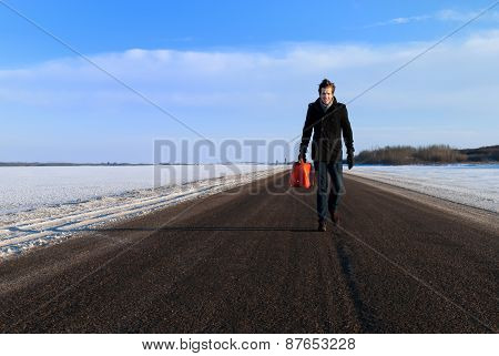 Man With Gas Can On Lonely Highway In Winter