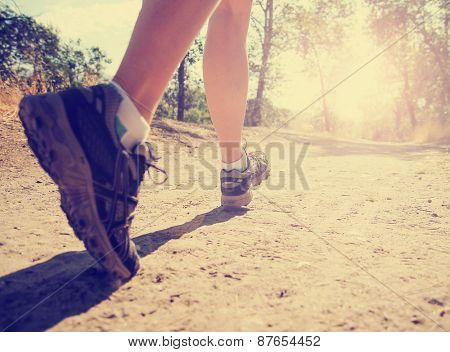 an athletic pair of legs running or jogging on a path during sunrise or sunset toned with a retro vintage instagram filter effect app or action