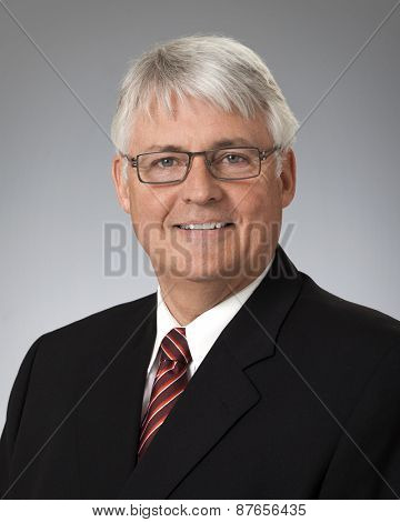 Studio portrait of mature businessman wearing black suit, against a gray background.
