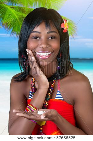 Closeup portrait of beautiful cheerful African female having fun on the beach, using suncream, enjoying happy summer vacation on seashore