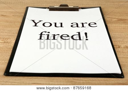 Message You're Fired on clipboard on wooden table, closeup