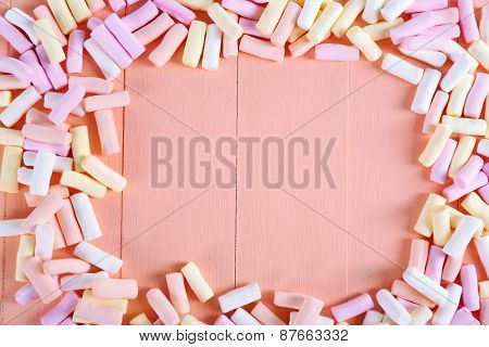 Frame of sweet candies on color wooden background
