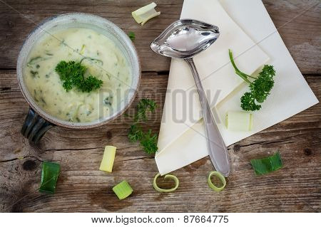 vegetable cream soup from soy with leek in a earthware bowl on a rustic wood poster