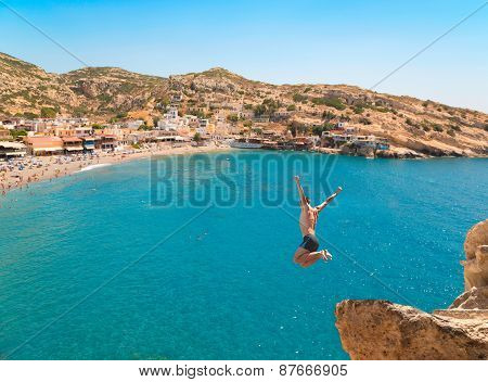 Young Man Jumping From The Cliff In The Sea.