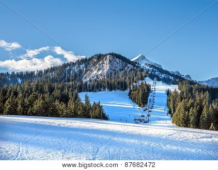 Mountain skiing slopes and ski lift at Hausberg top near Garmisch-Partenkirchen town in Bavarian Alpes in Germany with Zugspitze peak and blue sky at the backdrop on a clear winter day poster