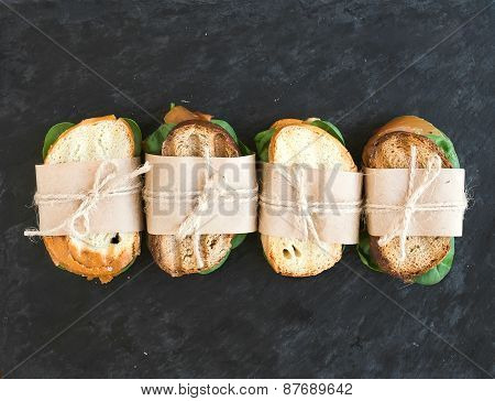 Chicken and spinach sandwiches wrapped in craft paper over a dark stone background with a copy space poster