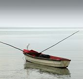 A lonely rowboat on calm seas against moody grey sky poster