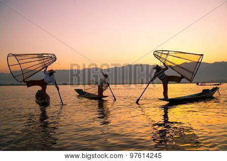 Three fishermen catches fish for food in sunrise in Inle Lake, Myanmar