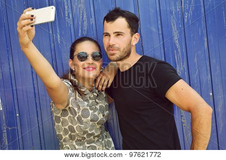 Happy couple taking self photo with smart phone. Selfie, love, relationship, young adult, concept. Image toned.