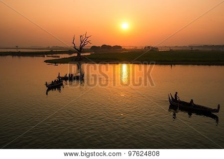 People sitting on boat to watch sunset in U-Bein bridge