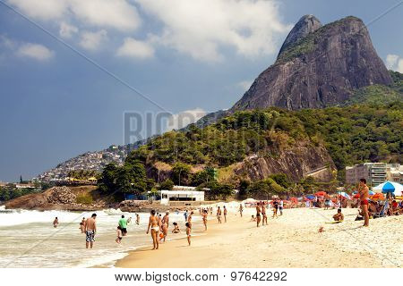 Ipanema beach in Rio de Janeiro with people swimming in the sea sunbathing and relaxing in the sun