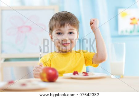 child eats healthy food showing his strength indoors