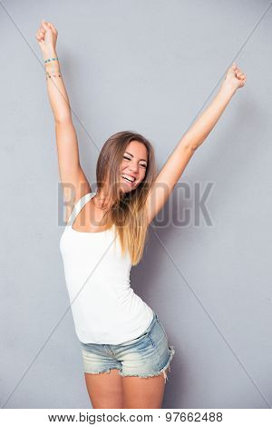 Cheerful young woman posing over gray background
