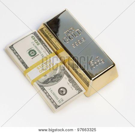 Cash for Gold Gold bullion bar beside stack of 100 dollar bills