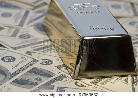 Cash for gold concept.  Gold bullion bar an pile of 100 hundred dollar bills