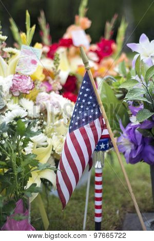 flag and flowers on grave