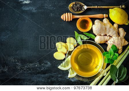 Cup of ginger tea with lemon and honey on slate plate