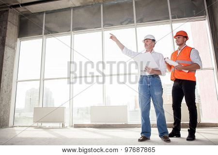Skilled construction team is working on plan of building