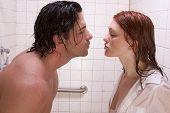 Loving affectionate nude young heterosexual couple in affectionate sensual kiss after taking shower. Mid adult Caucasian men in late 30s and young Caucasian redhead woman in early 20s poster