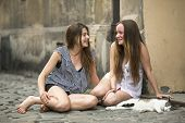 Happy girlfriends teenage girls sitting on the pavement with a cat. poster