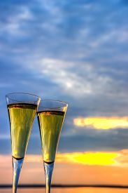Two Glasses Of White Wine Of Champagne On Sunset Sky