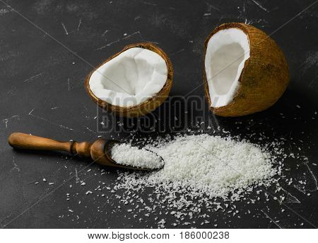 Coconut halves with shell with pulp. Coconut shavings on dark black background. Wooden spoon for Coconut shavings.