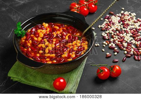 Stewed baked white and red beans in assortment in tomato sauce in a pan for baking beans. Raw dry white and red beans. Dark black background.