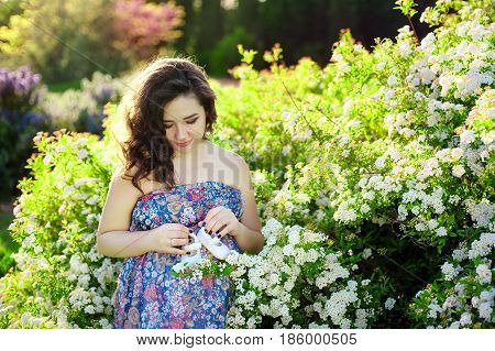 Pregnant woman belly holding baby booties. Healthy pregnancy. Newborn baby booties in parents hands. Pregnant woman belly