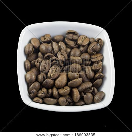 Roasted coffee beans in a small dish isolated on a black background