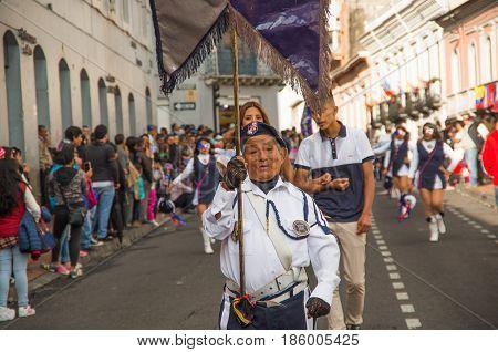 Quito, Ecuador - December 09, 2016: An unidentified man is holding a flag in a stick in parade in Quito, Ecuador.
