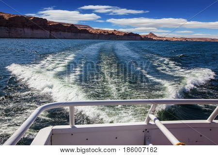 Walk on the tourist boat. Foam boat trail crosses the emerald waters. Red sandstone hills surround the lake Powell on the Colorado River
