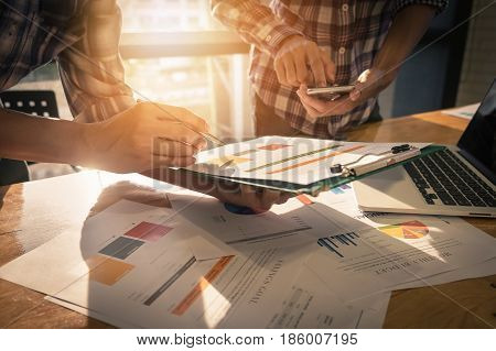 Close-up Of Two Businessman Hands Pointing At Turnover Graph While Discussing It On Wooden Desk In O