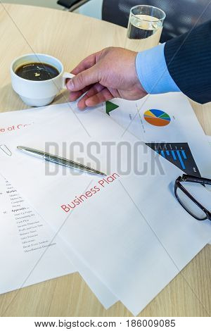 Businessman Grabbing A Cup Of Black Coffee Over A Business Plan On A Wood Table With A Glass Of Wate