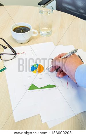 Businessman Analyzing A Pie Chart And Pointing His Silver Pen. His Coffee, Glasses And Water Are On