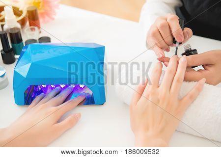 Female Hands Using Portable Uv Light Dryer