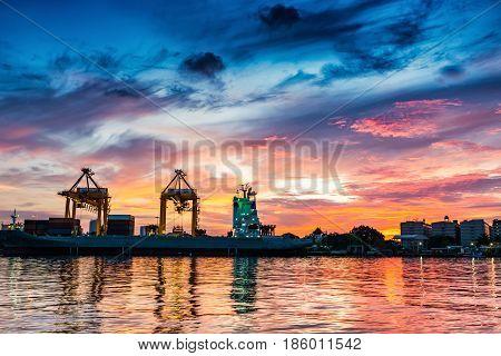 Cargo ship terminal at twilight scene Unloading crane of cargo ship terminal Sunset shot.