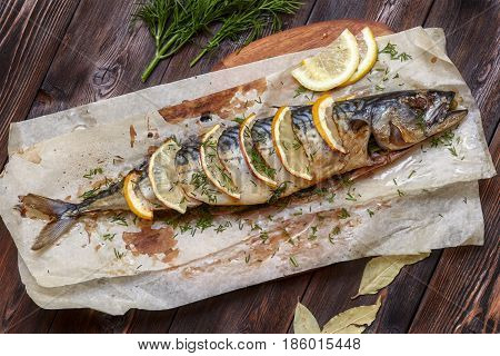 Whole baked mackerel or scomber fish with lemon and greens on paper dark wooden background top view