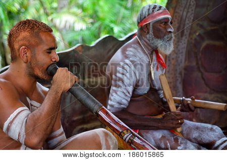 QUEENSLAND, AUS - APR 17 2016: Portrait of Yirrganydji Aboriginal men play Aboriginal music on didgeridoo and wooden instrument during Aboriginal culture show in Queensland Australia.