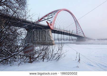 The bridge across the Ob river in Novosibirsk in the winter. The inscription on the sign: