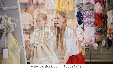 Shopping for kids - blonde little girl with mommy chooses dress in store of kids clothes, telephoto