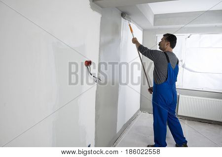Painter wearing bib overalls painting house interior.