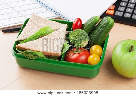 Office desk with supplies and lunch box with vegetables and sandwich