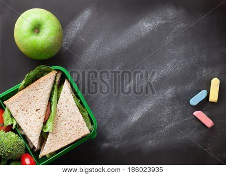 Lunch box with vegetables and sandwich. Kids take away food box and apple. Top view on blackboard with space for your text