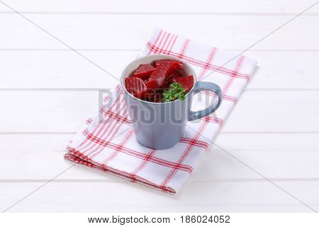 cup of sliced and pickled beetroot on checkered dishtowel